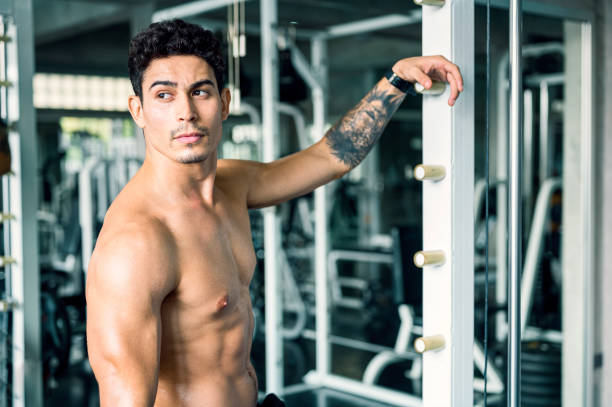 Healthy lifestyle, exercising and people concepts. Tattoo Muscular men with perfect abs excercise on a barbell, resting after weightlifting workout at gym.